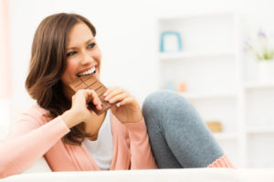 happy-woman-taking-bite-of-chocolate-bar_y4f5qu